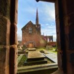 View through a doorway and out into a courtyard on a sunny day, viewing the chapter house and spire