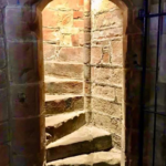 view through a doorway into an illuminated set of staircase, twisting to the left