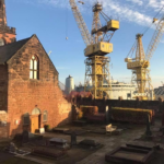 Two yellow cranes outside the walls of Birkenhead Priory. we see one face of a tall stone building and a brick spire behind that on the left hand side