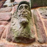 A weathered stone face of a man, an architectural detail on the wall of Birkenhead Priory