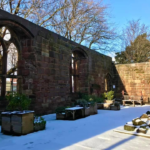 The interior of Birkenhead Priory, with the ground and plan pots covered in a light dusting of snow