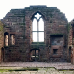 Ruins of a chapel-like space, with a large window with no glass in it. The building is brick and has no roof.