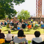 People sitting and watching a performance outside on a lawn. our view is behind all of them, towards the performance. It's a sunny day and people are either sitting on their own chairs or on picnic blankets