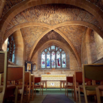A view of a chapel looking straight towards the altar, covered with a light cloth, with a vaulted stone ceiling