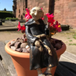 A model of a monk in a black robe sitting on a plant pot with a red flower behind him, in a sunny outdoor location.
